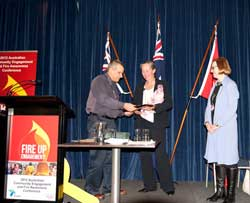 Frances Crown receiving the RFS Award for the Women's Training Program from RFS Deputy Commissioner Rob Rogers with Carolyn Chaplin (right) looking on